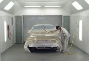 A person spray painting a car with a paint sprayer